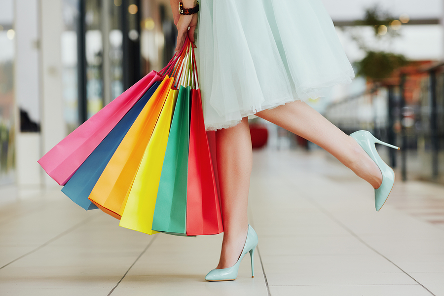 Woman's legs wearing light dress and hills standing with colorful shopping bags in shopping mall shopping concept standing on one leg.